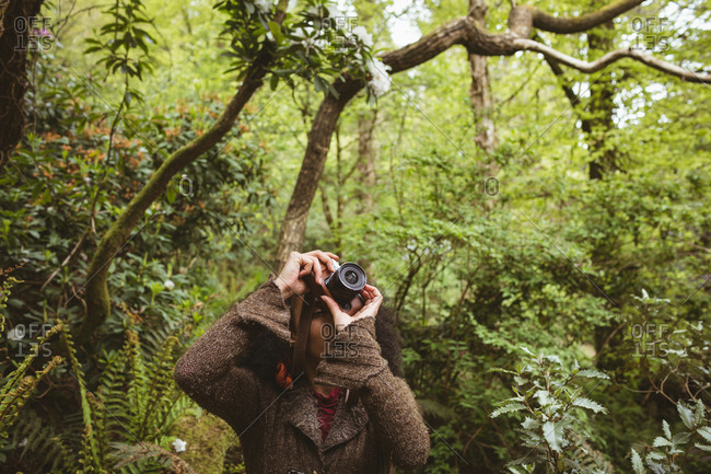Woman photographing from camera against trees at forest