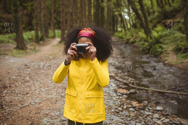 Woman photographing by stream while standing at forest