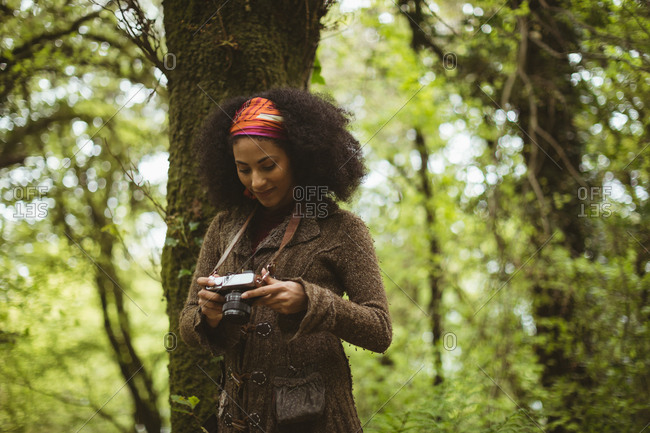 Young woman with camera by tree standing at forest