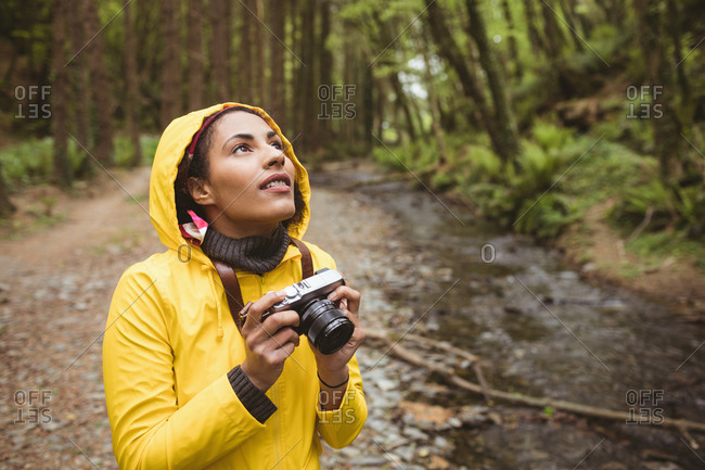 Young woman with camera looking up while standing by stream at forest