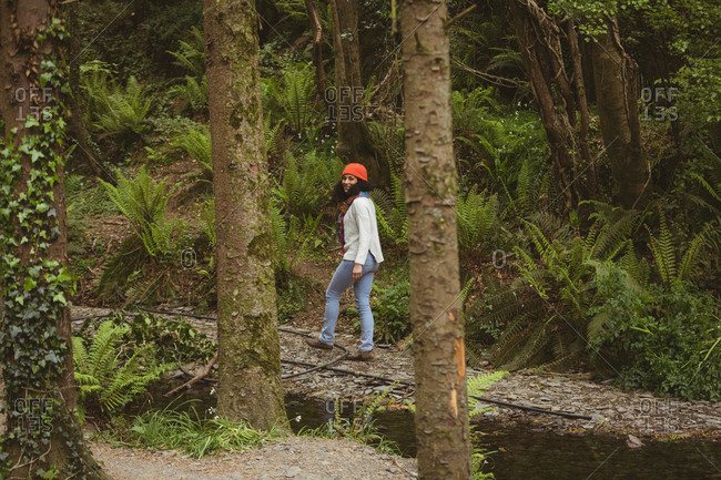 Full length of female hiker walking by trees at forest