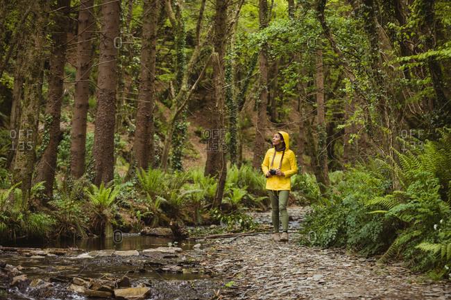 Full length of female hiker walking at forest
