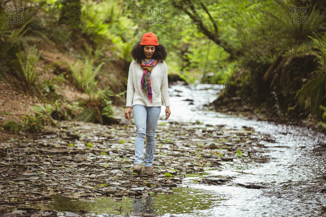 Full length of young female hiker walking by stream at forest