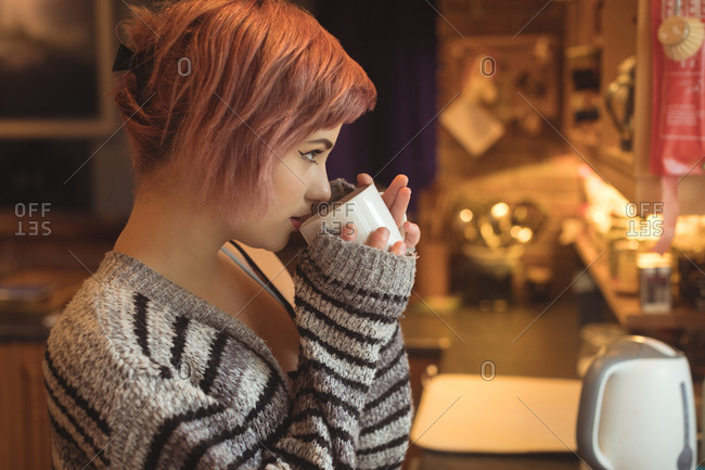 Young woman drinking coffee while looking away in kitchen at home