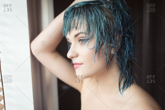 Close-up of thoughtful young woman with dyed hair looking away at home