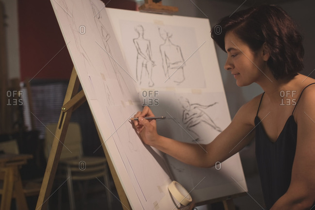 Female artist drawing a sketch on canvas in art studio