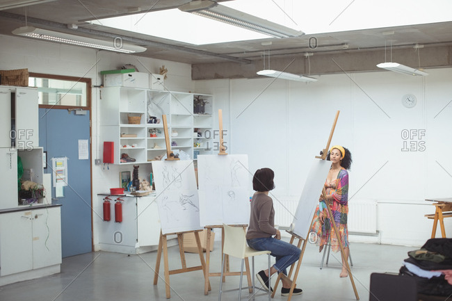 Female artist drawing a sketch of woman on canvas in art studio
