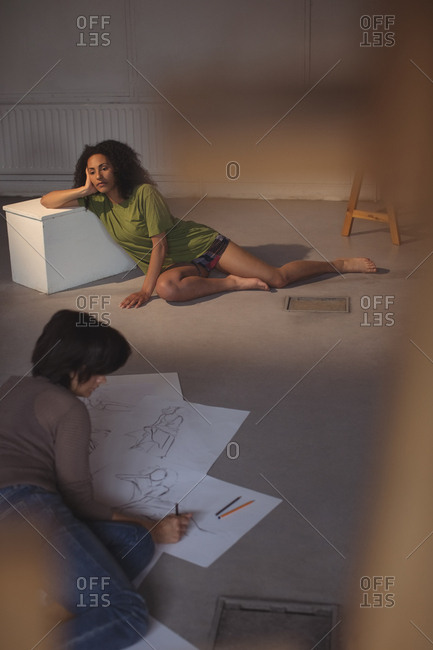 Female artist drawing a sketch of woman on paper in art studio
