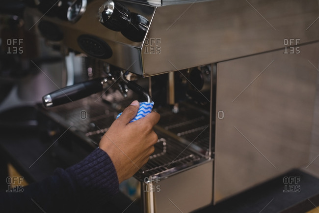 Cropped hand of owner operating coffee maker in cafe