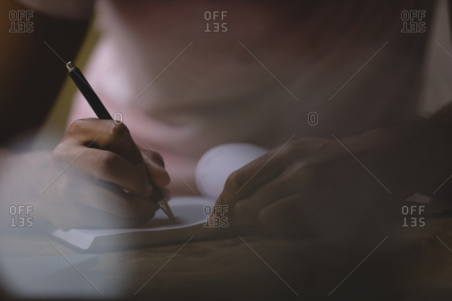 Close up midsection of young man writing in diary at cafe