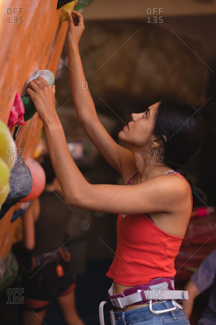 Side view of female athlete climbing wall in health club