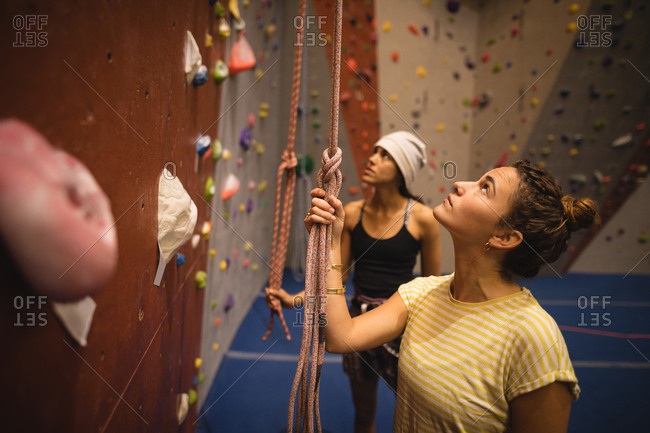 Female athletes looking up while standing by climbing wall in gym