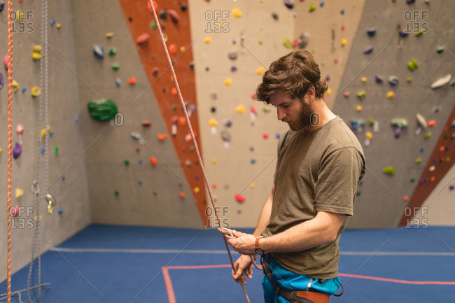 Side view of male athlete climbing wall in gym