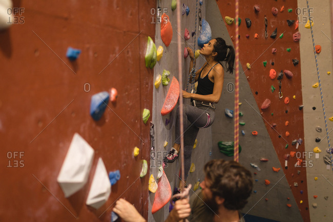 Athletes holding rope while climbing wall in gym