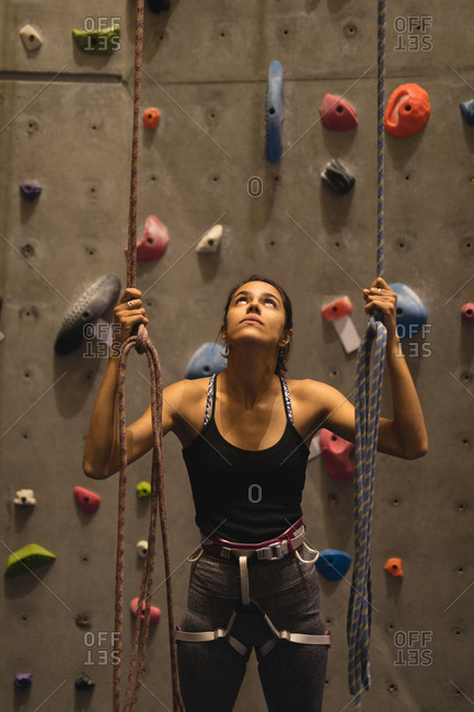 Confident female athlete holding ropes while standing against climbing wall in gym