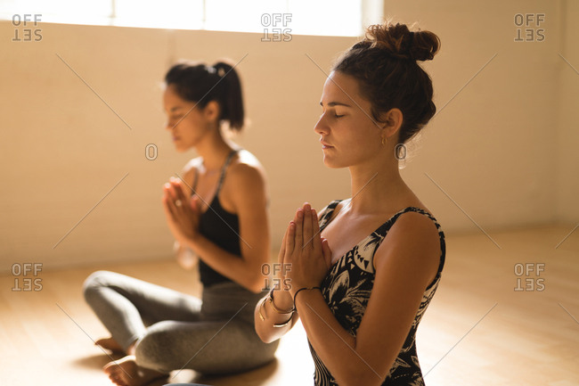 female friends meditating while sitting in yoga studio