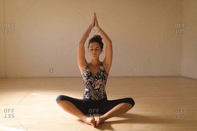 Young woman in prayer position meditating at yoga studio