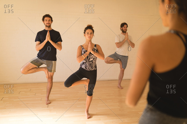 Yoga instructor guiding student in doing tree pose at yoga studio