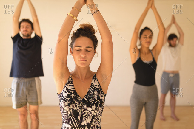 Yoga instructor with students mediating while standing in yoga studio