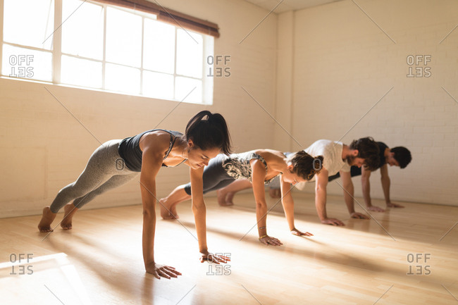 Yoga instructor with students exercising in health club