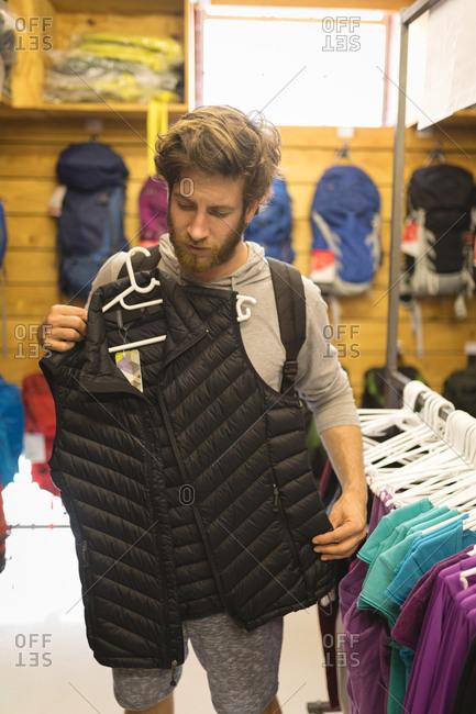 Young man examining lifeguard jackets in store