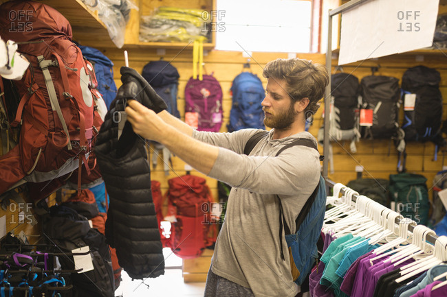 Side view of young man examining lifeguard jackets in store