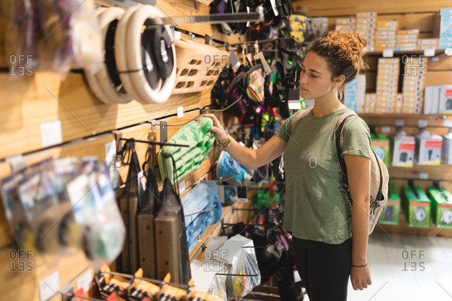 Young woman examining sports equipment in store