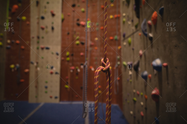 Rope hanging by climbing wall in gym