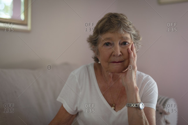 Portrait of senior woman sitting on sofa in living room