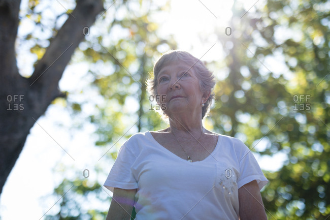 Thoughtful senior woman standing in park on a sunny day
