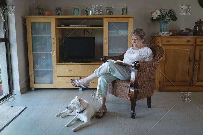 Senior woman reading novel in living room at home