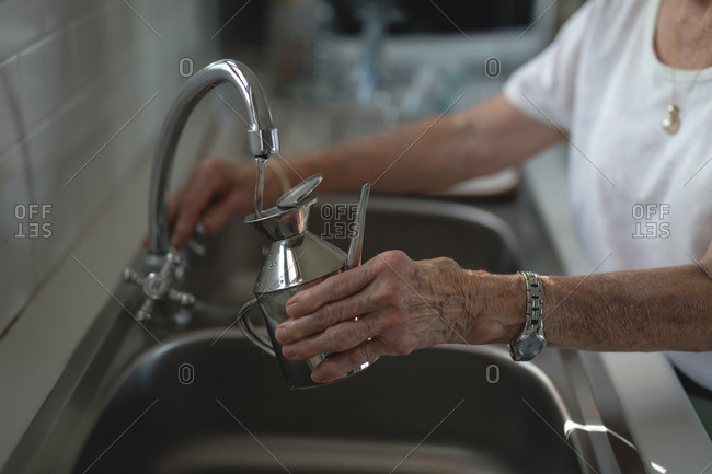 Senior woman filling jug with tap water in kitchen