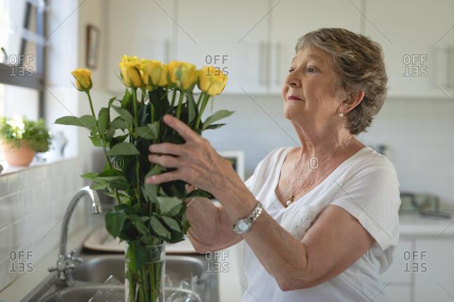 Senior woman preparing flower bouquet in kitchen at home