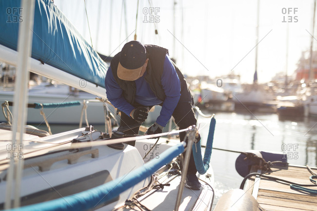 Man pulling winch rope on boat