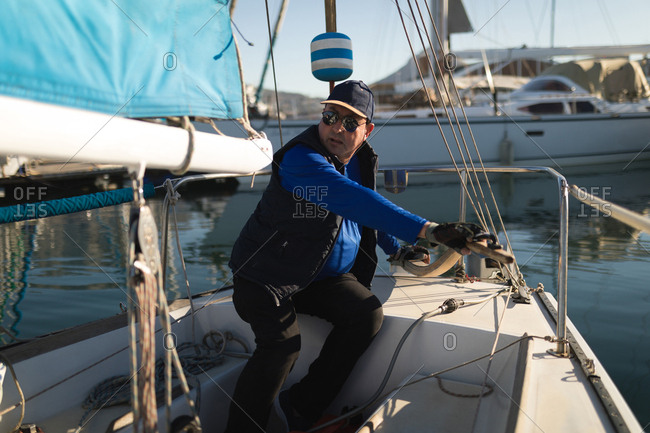 Yachtsman adjusting the rope tuning on a sunny day