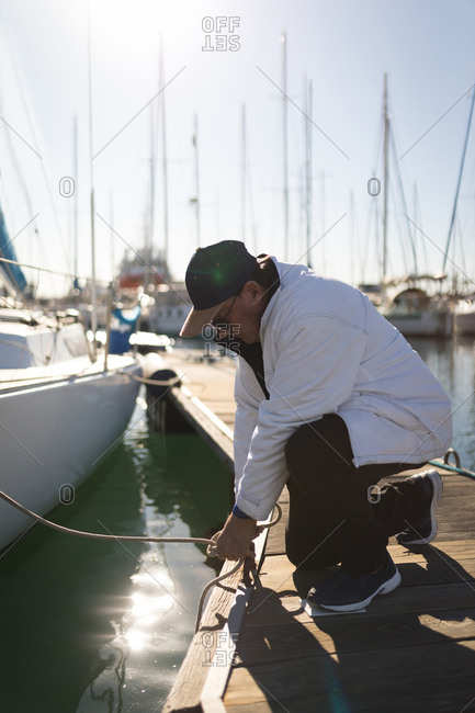 Yachtsman tying rope on the pier on a sunny day