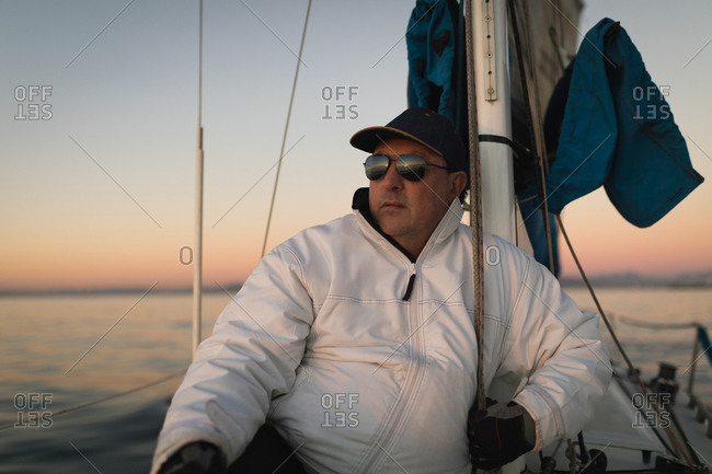 Yachtsman sitting on the boat on a sunset