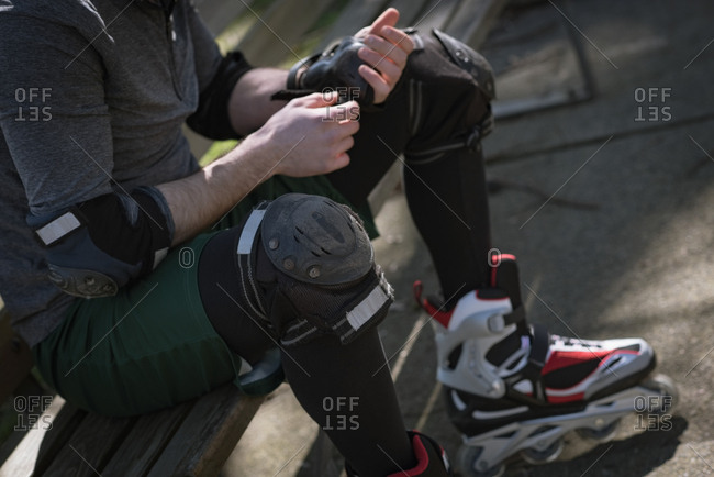 Tilt image of man wearing wrist pad while sitting on bench at park