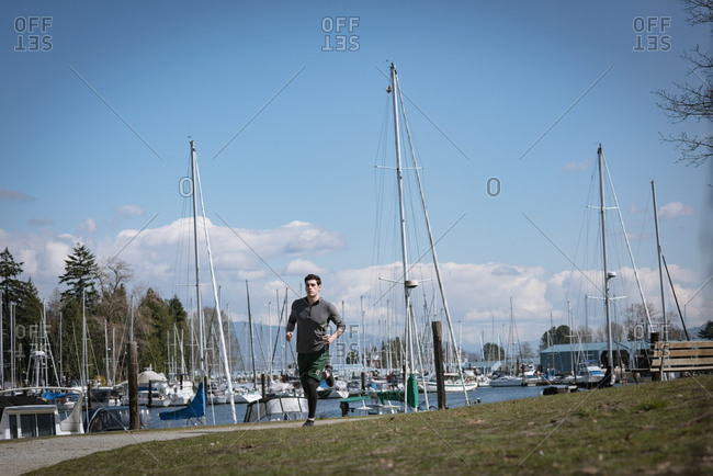 Full length of young man jogging on footpath by harbor against sky during sunny day