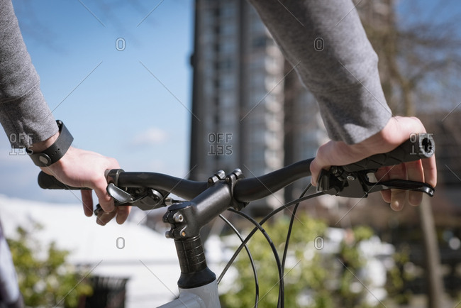 Cropped hands of young man holding bicycle during sunny day