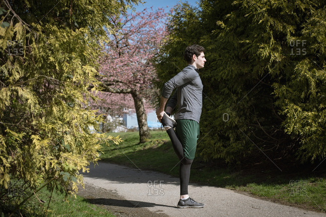 Side view of man doing stretching while standing on footpath at park during sunny day