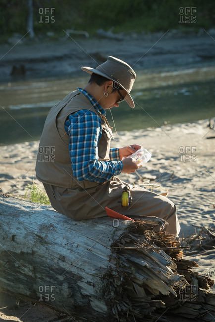 Side view of man looking at fishing bait while sitting on fallen tree trunk during sunny day