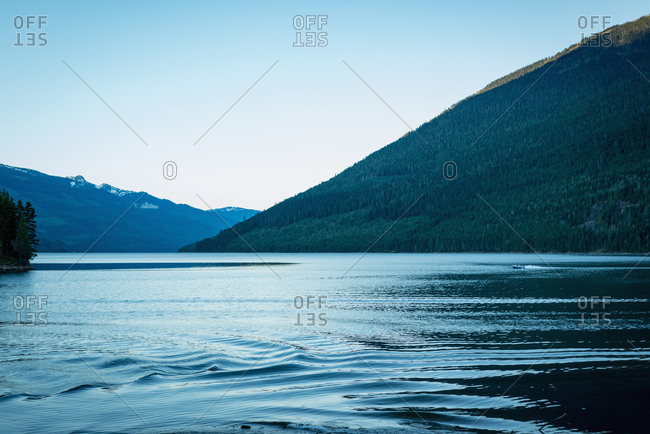 Scenic view of river by mountain against sky