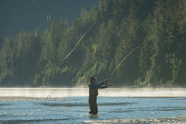 Side view of man casting fishing rod while standing in river