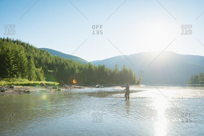 Mid distant view of man fishing in river against clear sky during sunny day