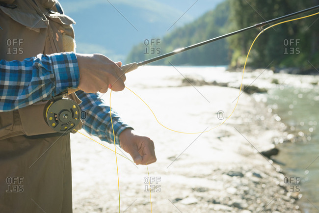 Mid section of man holding yellow thread while fishing in river against sky during sunny day