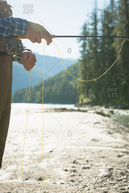 Cropped image of man fishing while standing on riverbank during sunny day