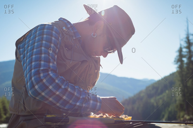 Man removing fishing bait from box while sitting against sky during sunny day