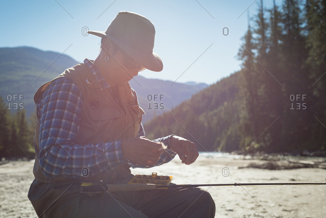 Young man tying fishing hook on rod while sitting at riverbank during sunny day