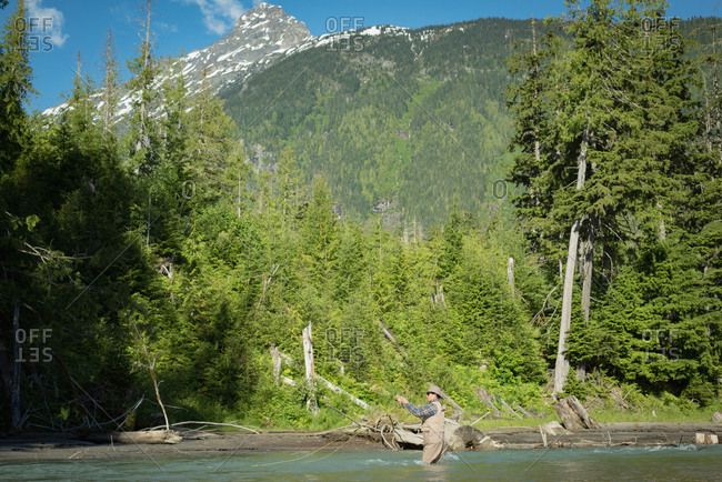 Mid distance view of man fishing in river against mountain